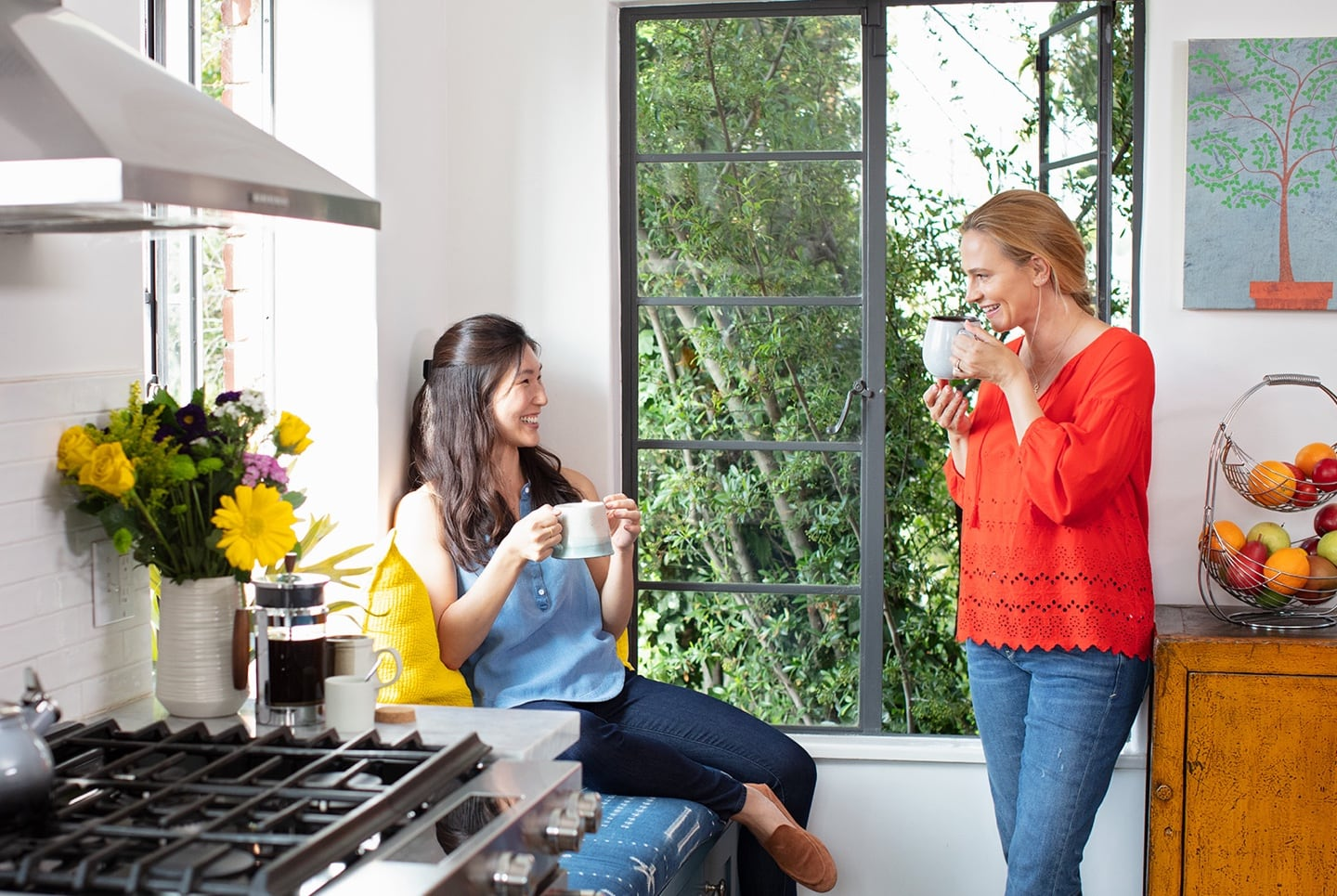 Two women talking in a kitchen while drinking tea or coffee